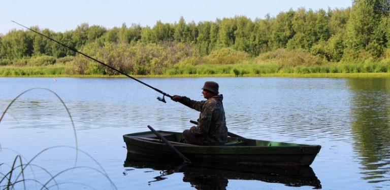 мужик на рыбалке удочкой бьет по воде